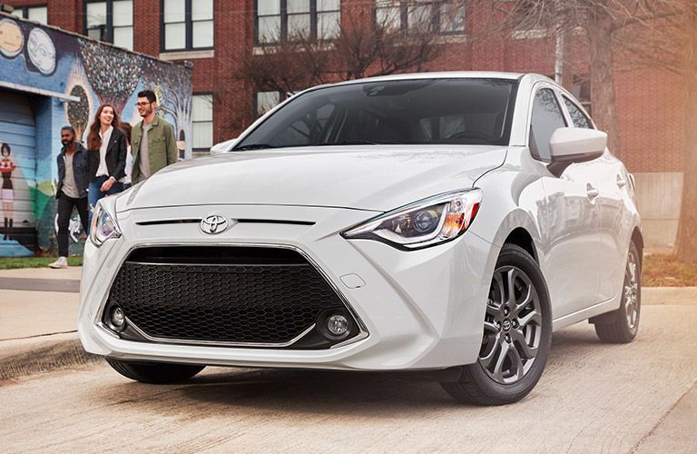 2019 Toyota Yaris exterior front fascia and drivers side low view parked on city road with friends walking on the sidewalk