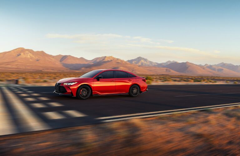 Side view of a red 2020 Toyota Avalon driving on open road