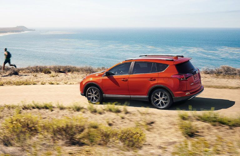 red 2016 Toyota RAV4 driving along the coast