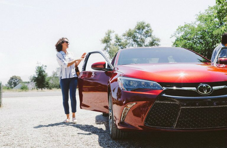 woman getting into Toyota Camry