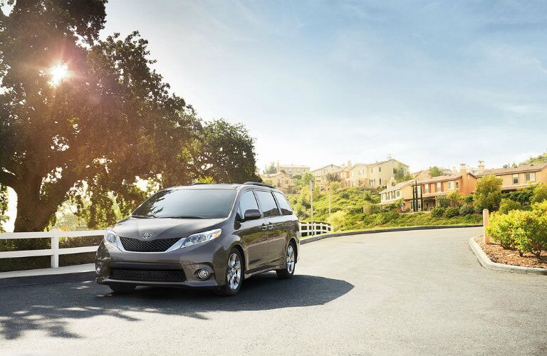 gray 2016 Toyota Sienna driving on suburban street