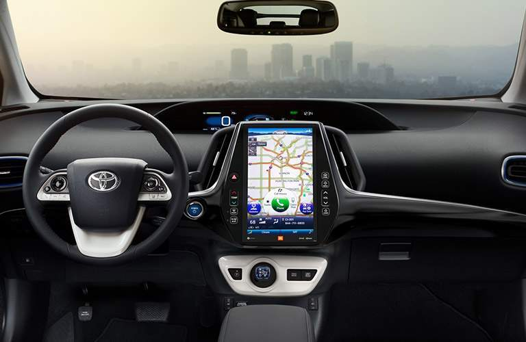 steering wheel and dashboard in 2018 Toyota Prius with hazy city view out windshield