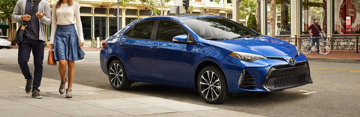 couple walking away from blue 2019 Toyota Corolla parked on street