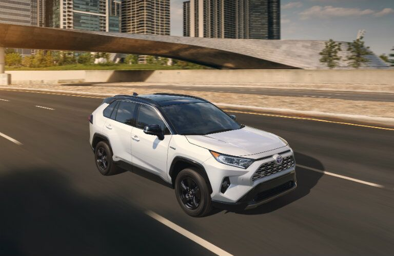 white 2019 Toyota RAV4 with black roof driving on highway