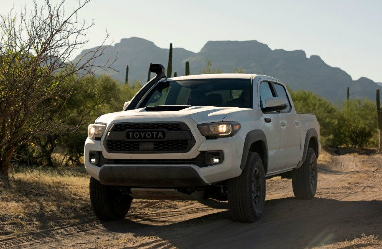 front side view of white 2018 Toyota Tacoma TRD Pro in the desert backed by mountains
