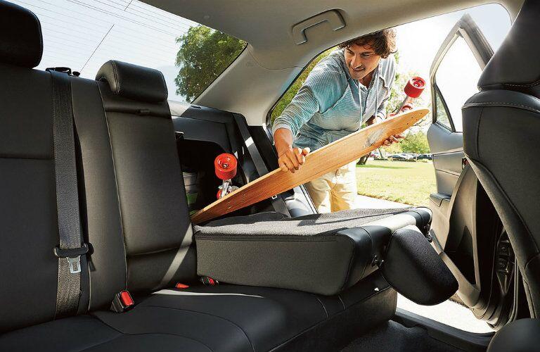 Man puts longboard in back seat of Corolla through folding seat