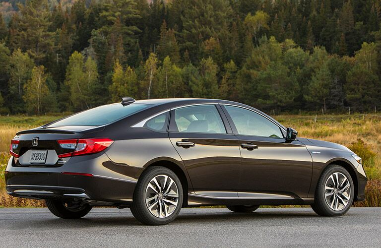 2018 Honda Accord Hybrid exterior back fascia and passenger side parked in lot with trees in background