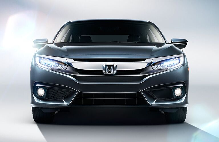 front view of gray honda civic with LED headlights on