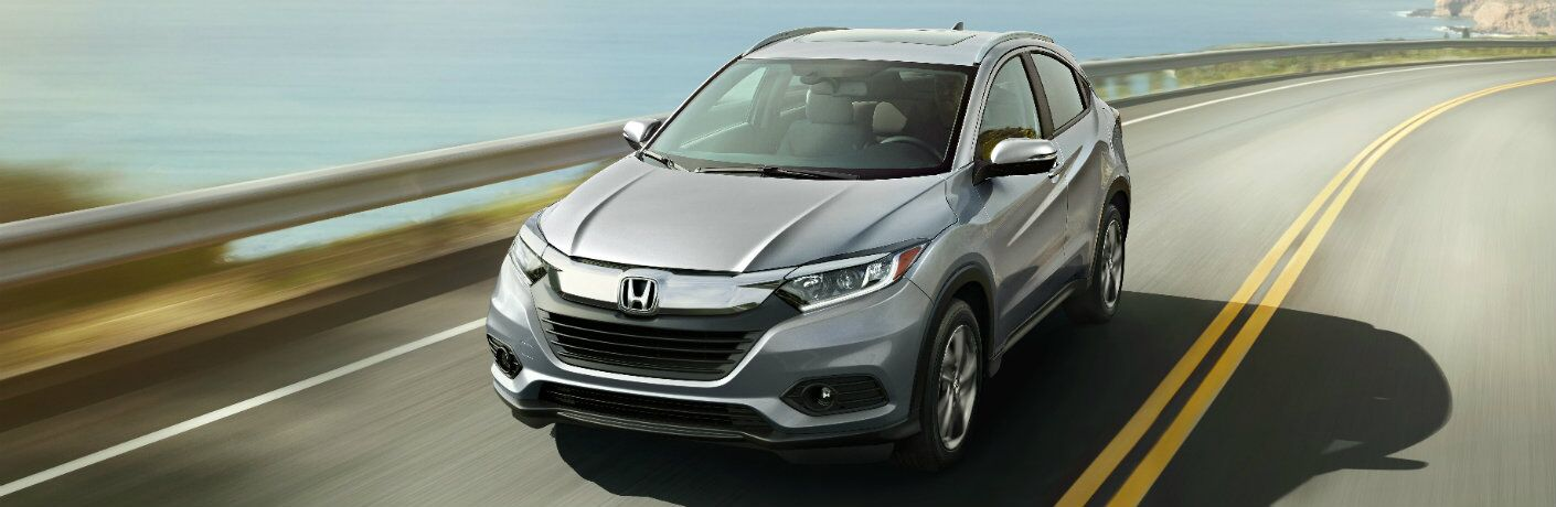 white honda hr-v driving on highway by water