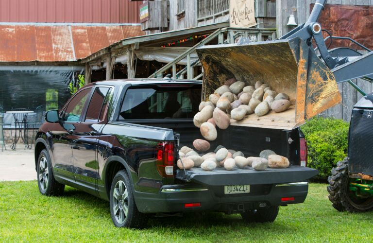 2019 Honda Ridgeline exterior back fascia and drivers side with machine dumping rocks into bed