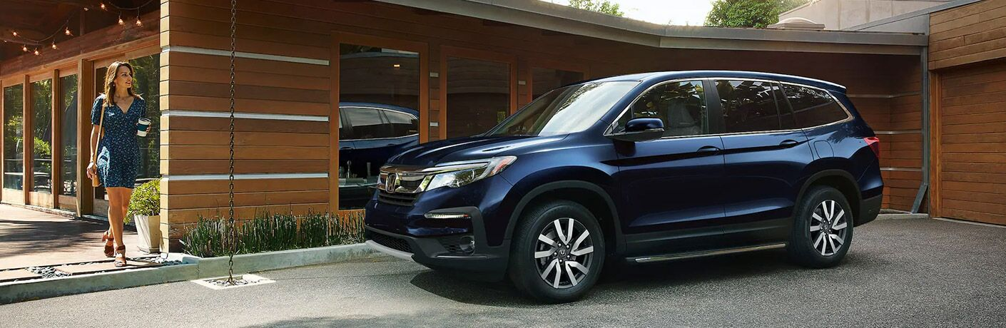 A woman entering a 2021 Honda Pilot parked in front of a building