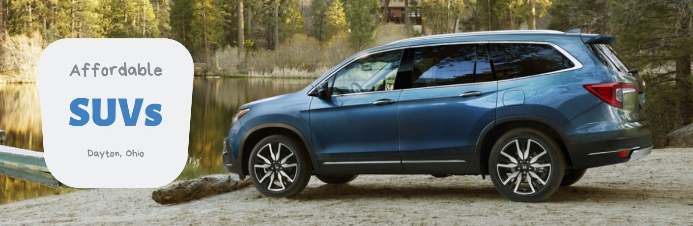 Affordable SUVs Dayton, OH, text next to a driver side exterior view of a blue 2019 Honda Pilot