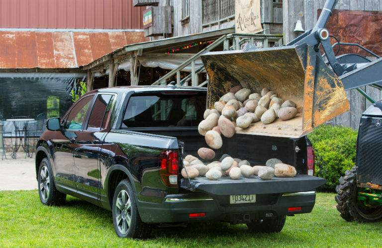 Cargo bed of the 2019 Honda Ridgeline being loaded with large rocks