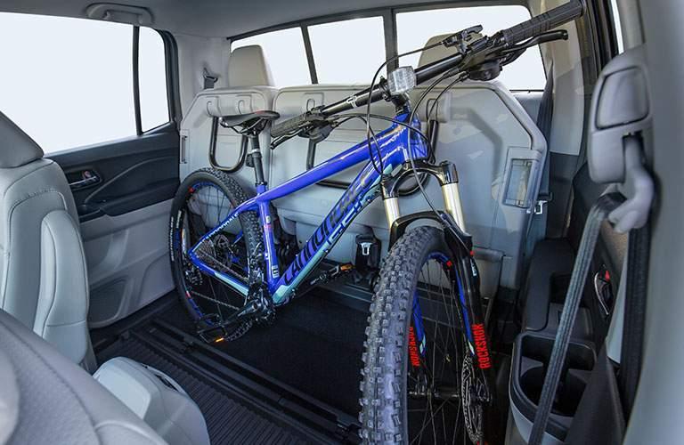 Blue bike in the back seat of 2018 Honda Ridgeline's interior