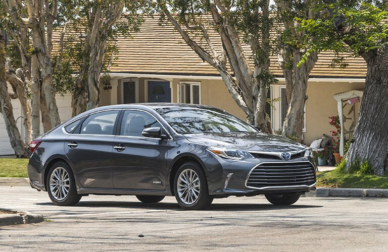 silver 2018 toyota avalon hybrid driving on residential street