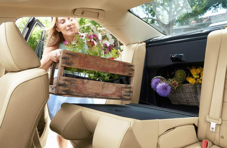 Woman loading a basket of flowers into the rear of the 2017 Toyota Camry