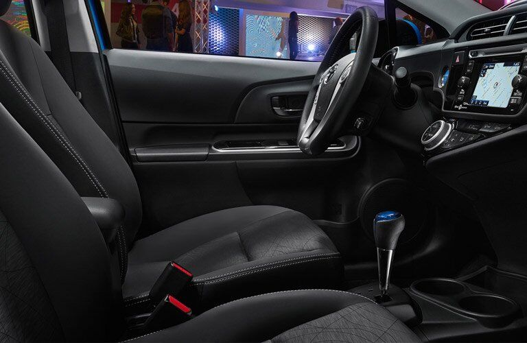 front interior driver seat of 2018 toyota prius c including steering wheel and center interface