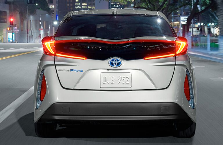rear bumper of silver 2018 toyota prius prime driving in city at night