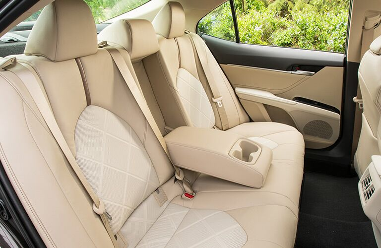 rear seating of 2018 toyota camry hybrid with cupholders and armrest