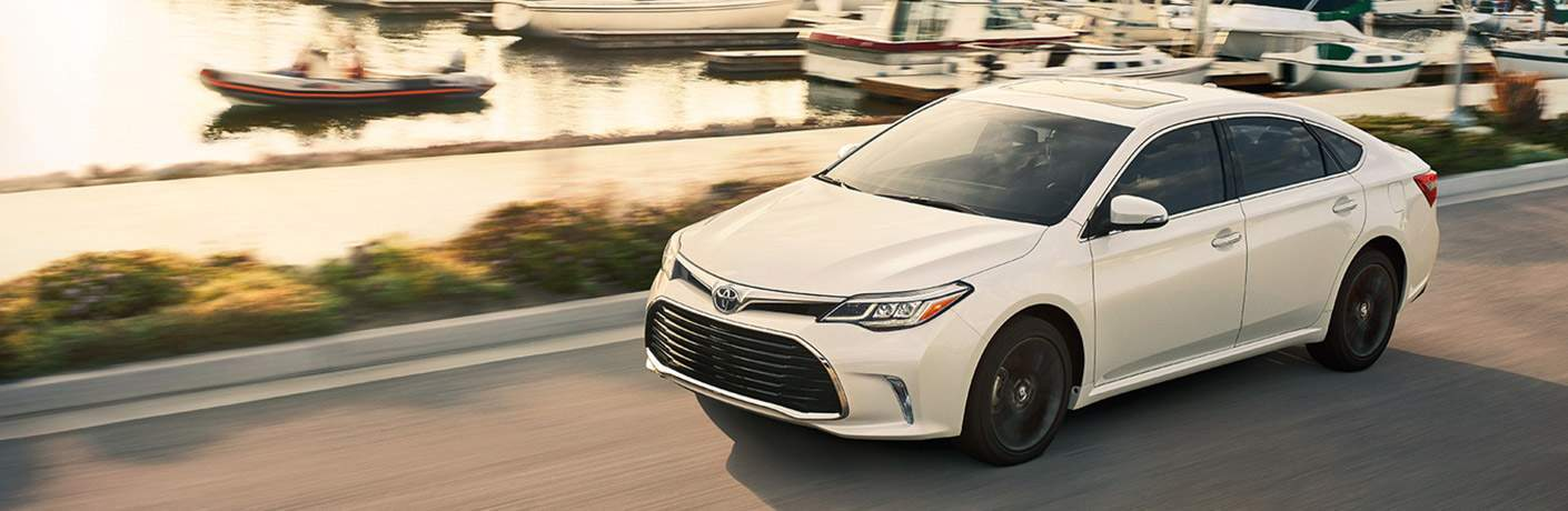 white 2018 toyota avalon driving along road past water and boats