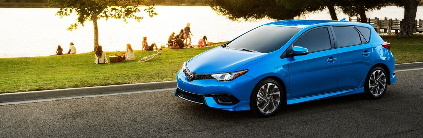 blue 2018 toyota corolla im parked on street with park of people and lake behind it