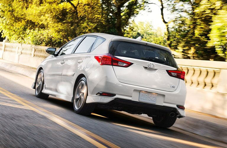rear view of white 2018 toyota corolla im driving on road surrounded by trees