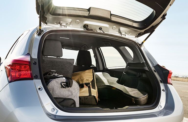 rear view of silver 2018 toyota corolla im with hatchback open and luggage in cargo space