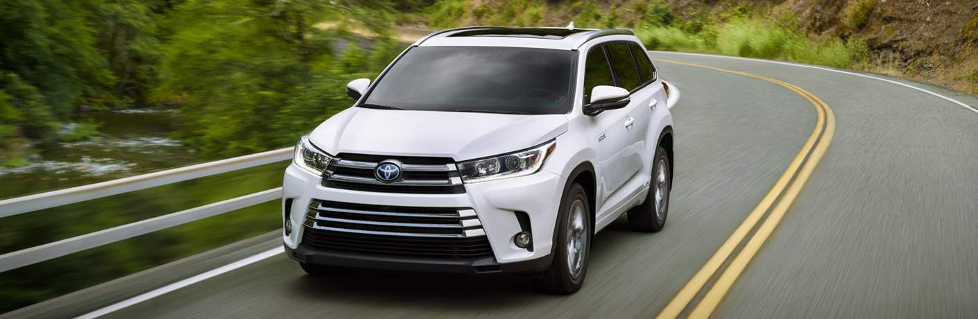 white 2018 toyota highlander hybrid driving on highway