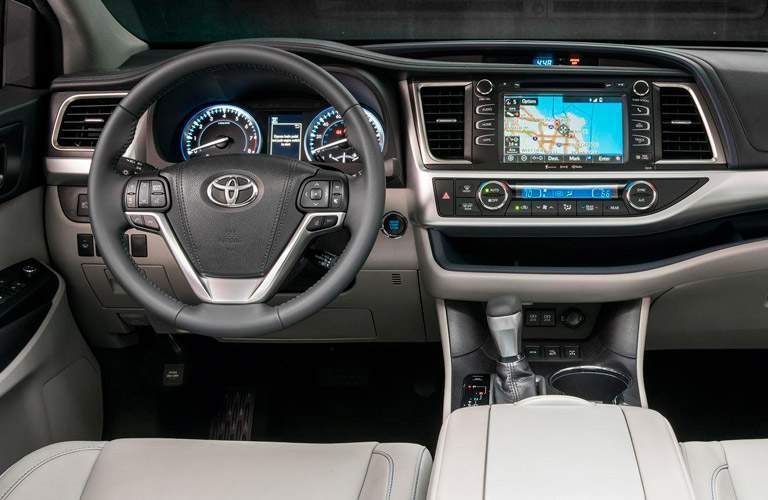 front driver side interior of 2018 toyota highlander hybrid including steering wheel and infotainment system