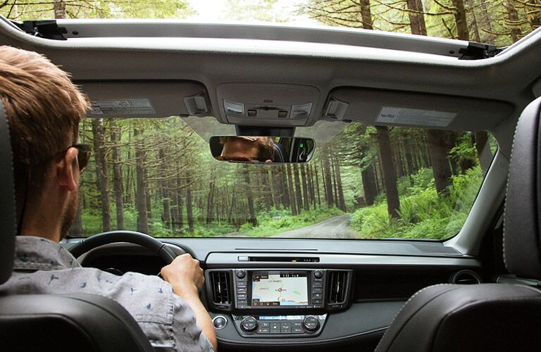 view of interior of 2018 toyota rav4 hybrid driving through forest including moonroof and infotainment system