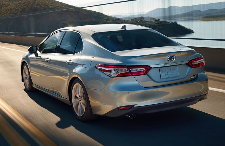 rear view of silver 2018 toyota camry hybrid driving on bridge