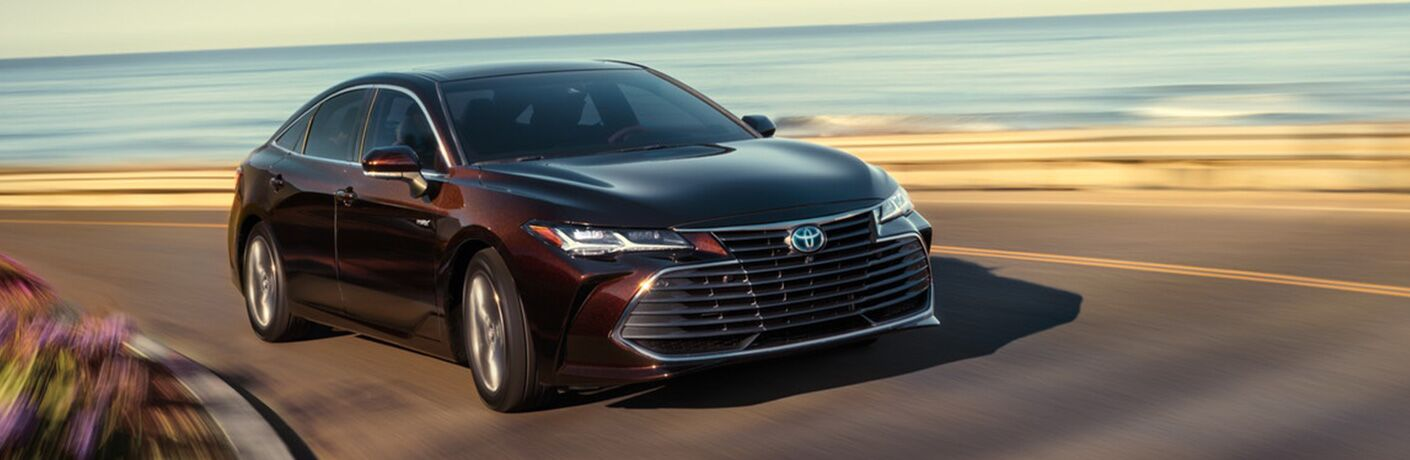 red 2019 toyota avalon driving on road with ocean behind it