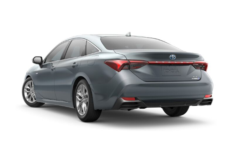 rear and side view of silver 2019 toyota avalon hybrid against white background