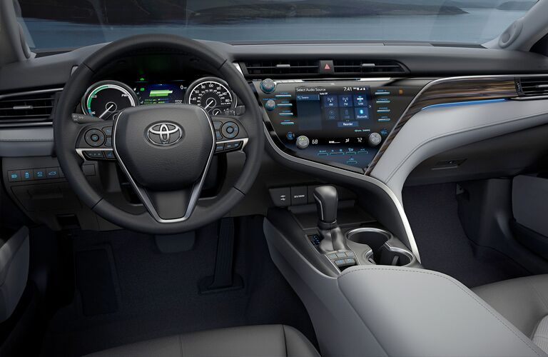 front interior of 2019 toyota camry hybrid including steering wheel and infotainment system