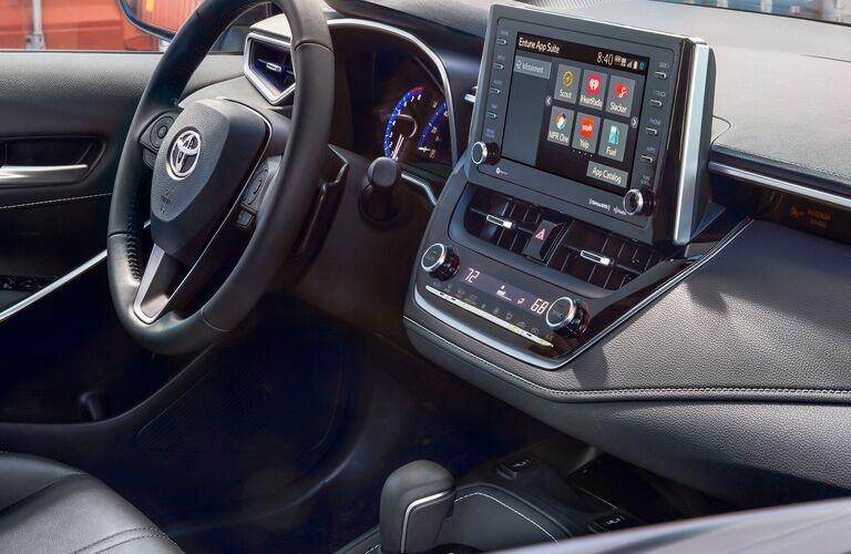 side view of front interior of 2019 toyota corolla hatchback including steering wheel and infotainment system