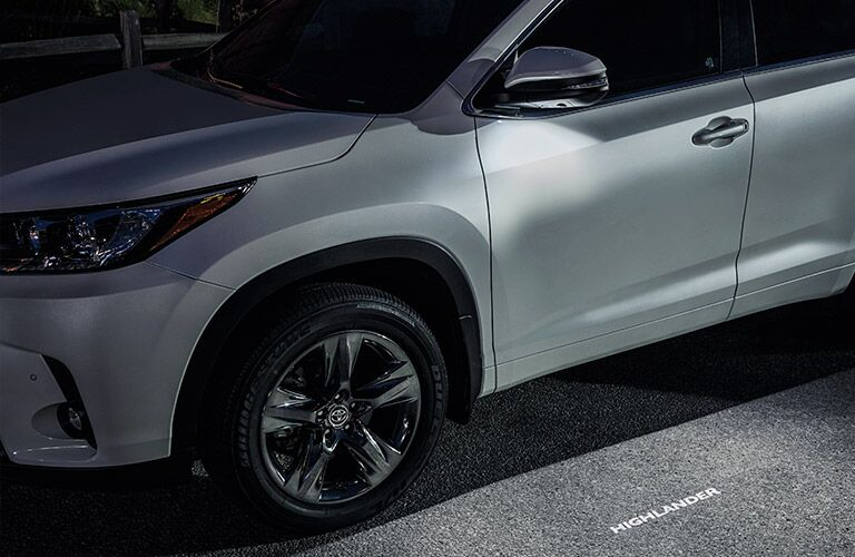 side view of white 2019 toyota highlander with puddle lights