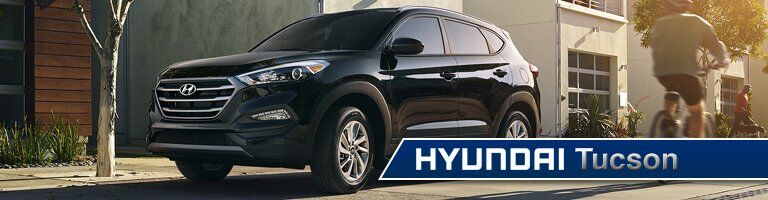 Driver's side exterior view of a black Hyundai Tuscon