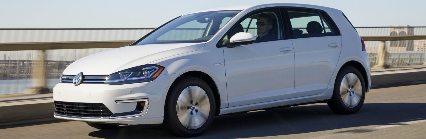 White 2018 Volkswagen e-Golf driving across a bridge