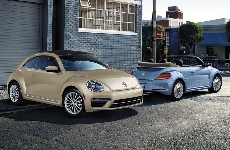 Tan 2019 Volkswagen Beetle and blue 2019 Volkswagen Beetle Convertible parked next to a blue building