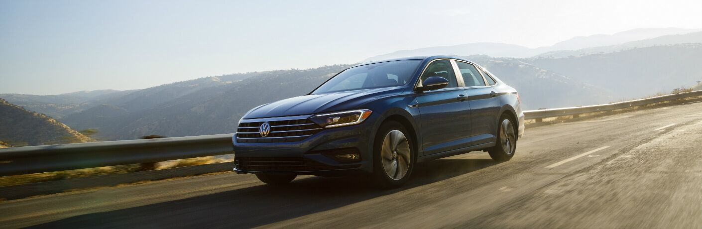 Blue 2019 Volkswagen Jetta Driving on a Mountain Highway