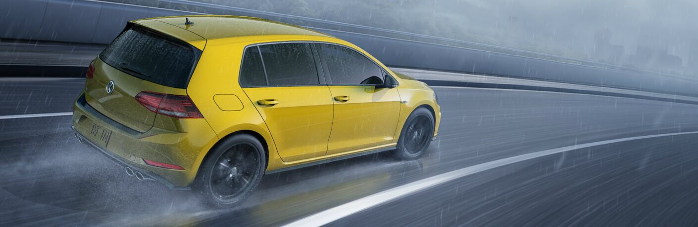 Yellow 2019 Volkswagen Golf R driving through the rain