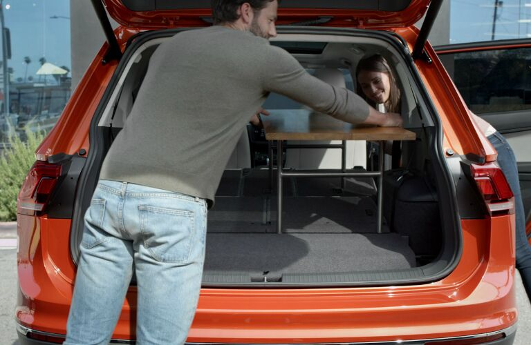 A Man and a Woman Loading a Table in the Cargo Area of a 2019 Volkswagen Tiguan