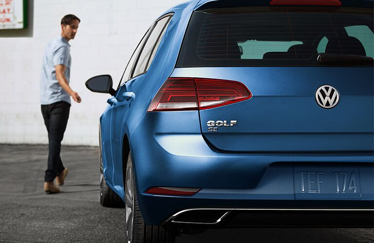 A man walking away from a blue 2020 Volkswagen Golf