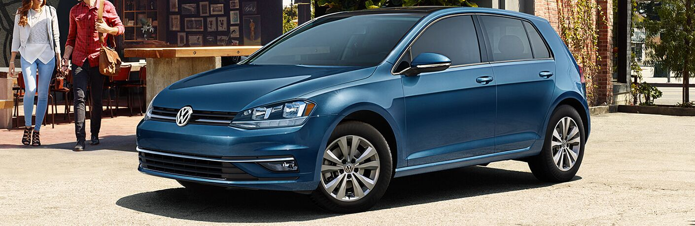 Blue 2020 Volkswagen Golf parked near the outdoor seating area of a restaurant