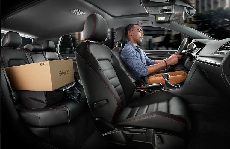A man driving a 2020 Volkswagen Golf GTI with a box in the rear seat area