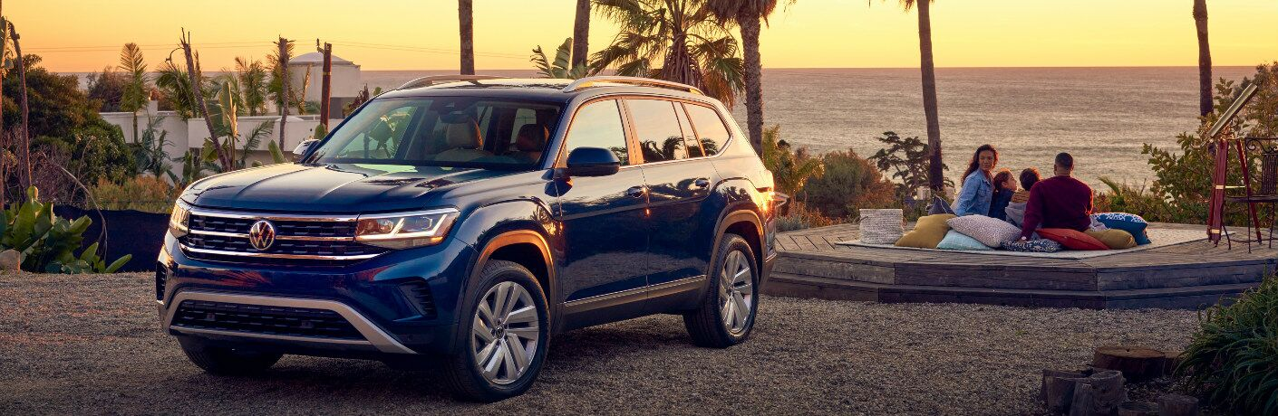 A family watching a sunset near a blue 2021 Volkswagen Atlas