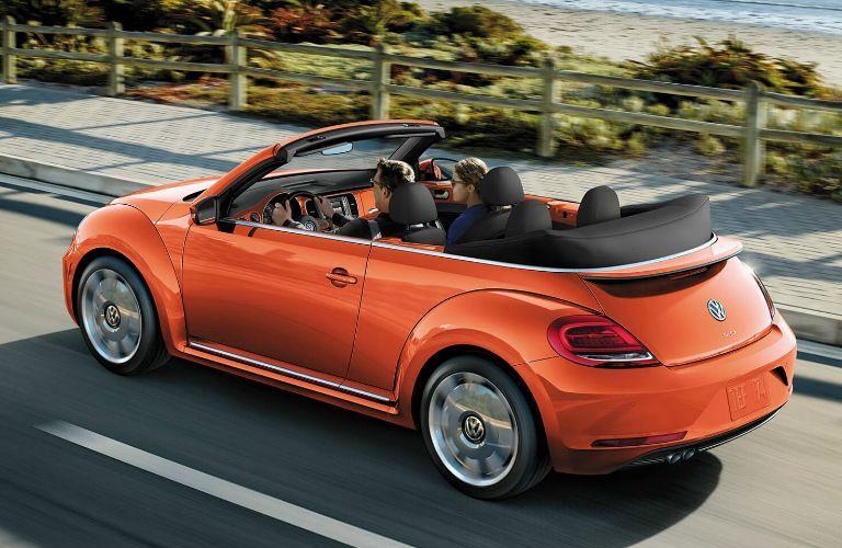 Orange 2019 Volkswagen Beetle Convertible driving on a coastal road