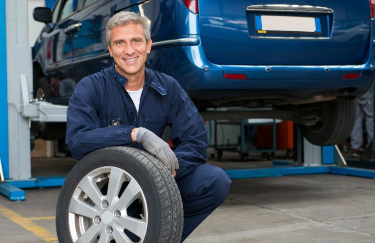 Mechanic resting on a tire