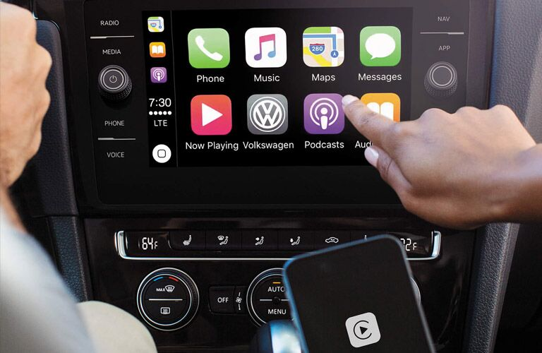 A finger touching the infotainment system touchscreen in a 2019 Volkswagen Golf GTI