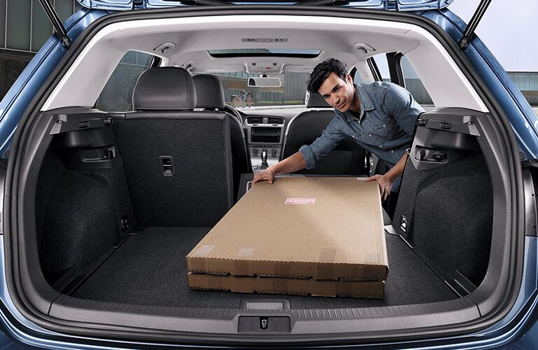 A man placing a box in the cargo area of a blue 2019 Volkswagen Golf